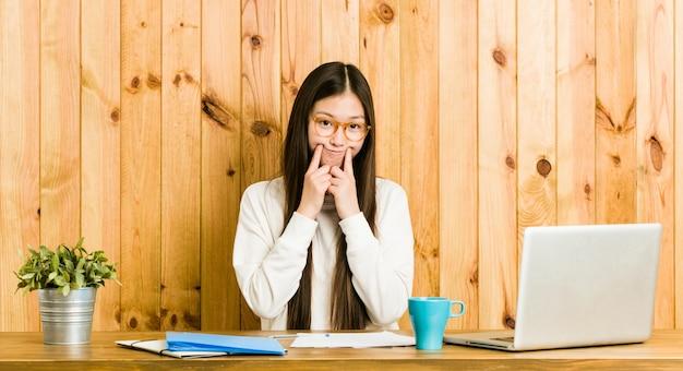 Jonge chinese vrouw die op haar bureau bestudeert dat tussen twee opties twijfelt.