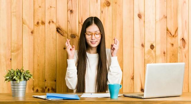 Jonge chinese vrouw die op haar bureau bestudeert dat vingers kruist voor het hebben van geluk