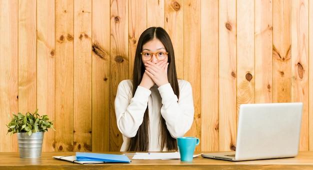Jonge chinese vrouw die op haar bureau bestudeert geschokt behandelend mond met handen.