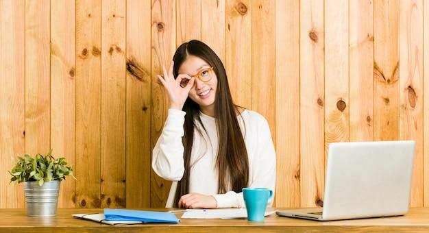 Jonge chinese vrouw die op haar bureau bestudeert opgewekt het houden van ok gebaar op oog.