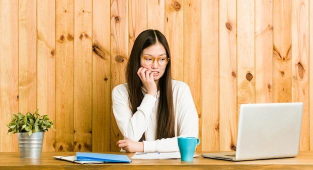 Jonge chinese vrouw die op haar bureau bijt vingernagels, nerveus en zeer bezorgd.