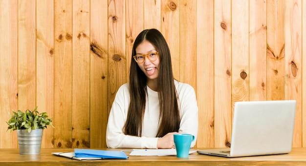 Jonge chinese vrouw die op haar bureau grappige en vriendschappelijke uitsteekt tong bestudeert.