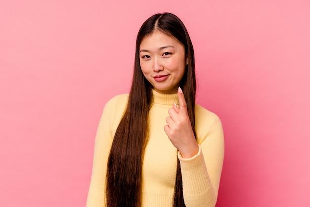 Jonge chinese vrouw die op roze achtergrond wordt geïsoleerd die met vinger naar u richt alsof uitnodigend kom dichterbij.