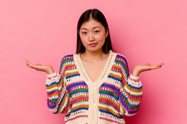Jonge chinese vrouw die op roze muur wordt geïsoleerd die en schouders ophaalt in vragend gebaar