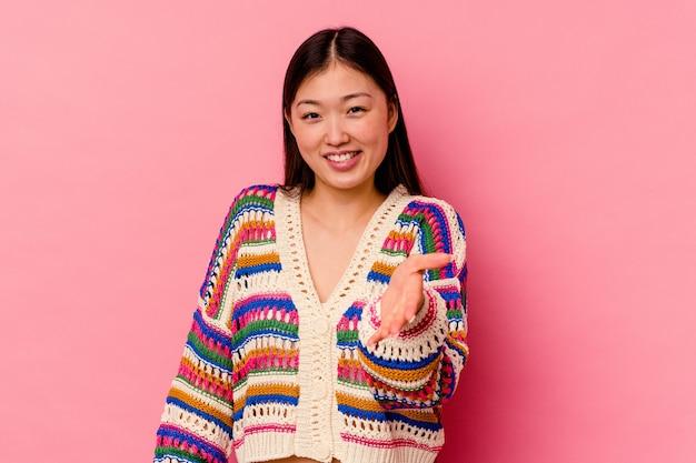 Jonge chinese vrouw die op roze muur wordt geïsoleerd die hand aan voorzijde in groetgebaar uitrekt