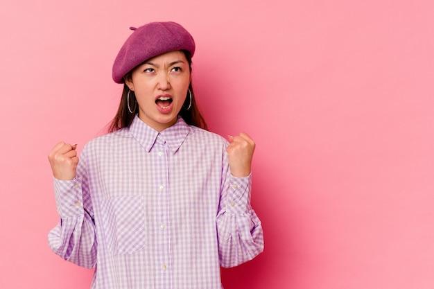 Jonge chinese vrouw die op roze muur wordt geïsoleerd die vuist opheft na een overwinning, winnaarconcept.