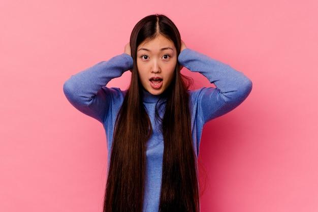 Jonge chinese vrouw die oren behandelt met handen die niet te hard geluid proberen te horen.