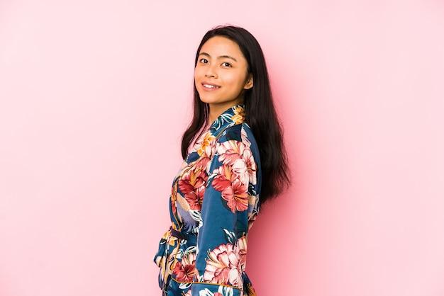 Jonge chinese vrouw die pijama draagt die zijdelings eruit ziet