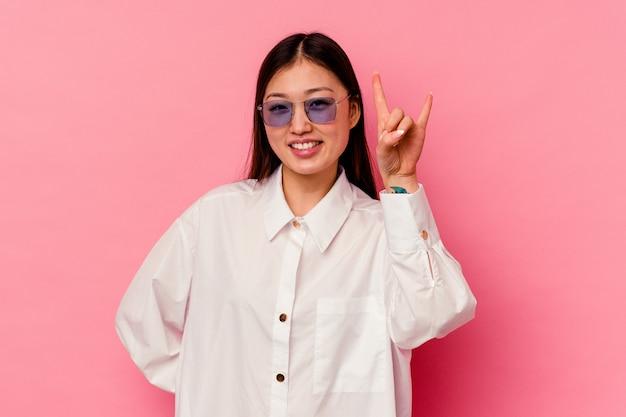 Jonge chinese vrouw die rotsgebaar met vingers toont