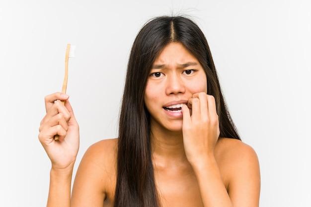 Jonge chinese vrouw die tandenborstel geïsoleerde het bijten vingernagels, zenuwachtig en zeer bezorgd houdt.