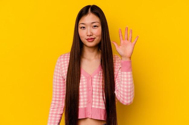 Jonge chinese vrouw die vrolijk tonend nummer vijf met vingers glimlacht.