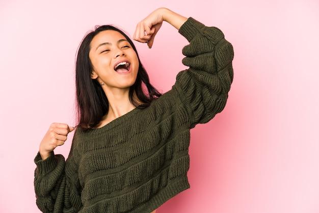 Jonge chinese vrouw die vuist opheft na een overwinning, winnaarconcept.