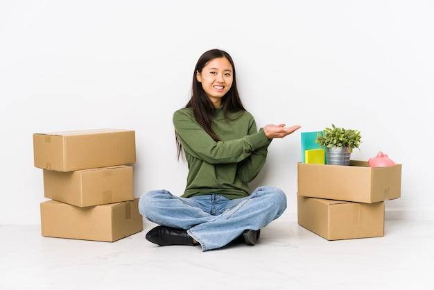 Jonge chinese vrouw die zich naar een nieuw huis beweegt dat een exemplaarruimte op een palm houdt.