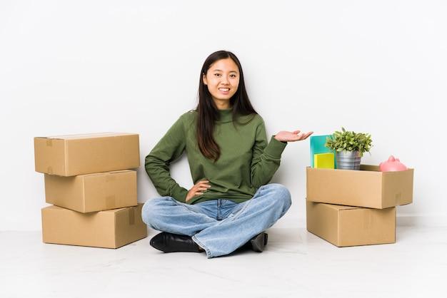 Jonge chinese vrouw die zich naar een nieuw huis beweegt dat een exemplaarruimte op een palm toont en een andere hand op taille houdt.