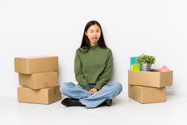 Jonge chinese vrouw die zich naar een nieuw huis beweegt dat grappig en vriendschappelijk tong uitsteekt.