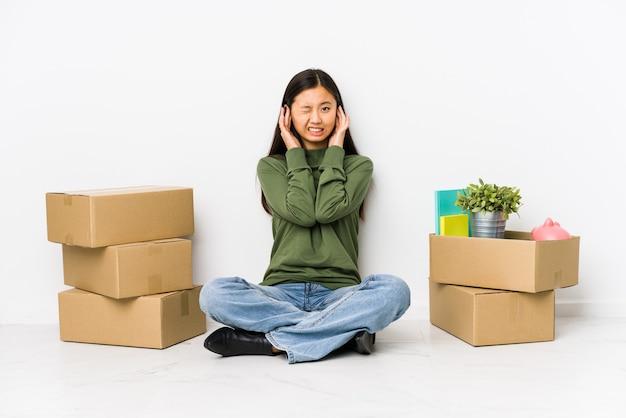 Jonge chinese vrouw die zich naar een nieuw huis beweegt dat oren behandelt met handen.