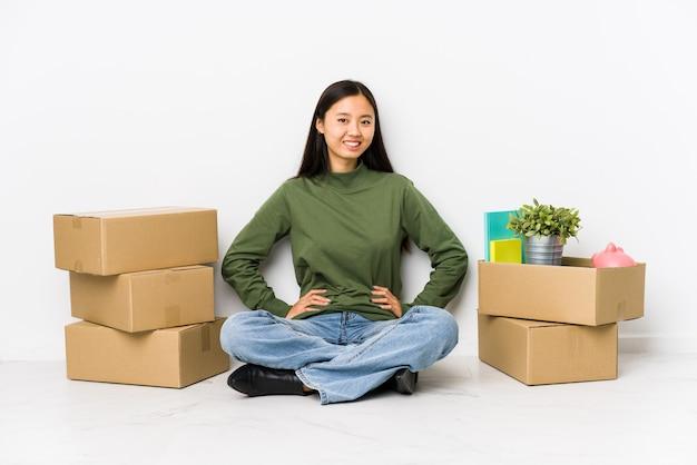 Jonge chinese vrouw die zich naar een nieuw huis beweegt die zeker handen op heupen houdt.