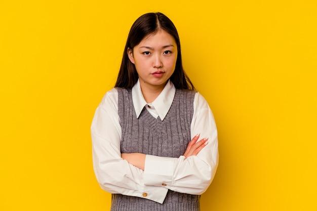Jonge chinese vrouw fronsend gezicht in ongenoegen, houdt armen gevouwen.