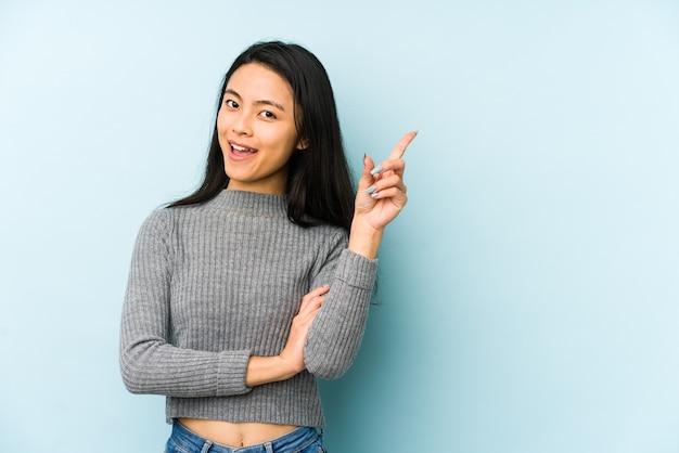 Jonge chinese vrouw geïsoleerd op een blauwe muur glimlachend vrolijk wijzend met wijsvinger weg.