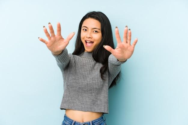 Jonge chinese vrouw geïsoleerd op een blauwe muur voelt zich zelfverzekerd met een knuffel