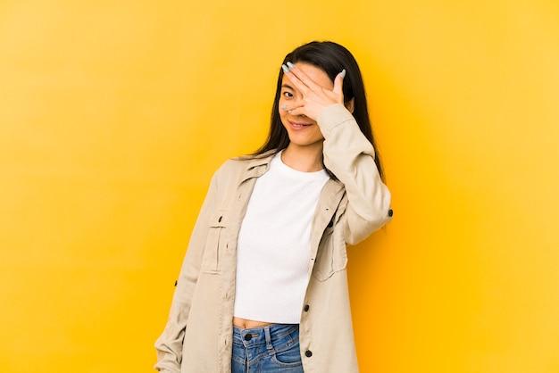 Jonge chinese vrouw geïsoleerd op een gele muur knipperen door vingers, beschaamd bedekkend gezicht.
