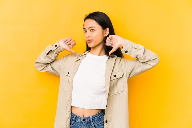 Jonge chinese vrouw geïsoleerd op een gele muur voelt zich trots en zelfverzekerd, voorbeeld om te volgen.