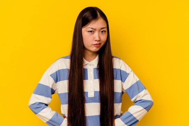 Jonge chinese vrouw geïsoleerd op geel fronsend gezicht in ongenoegen, houdt armen gevouwen.