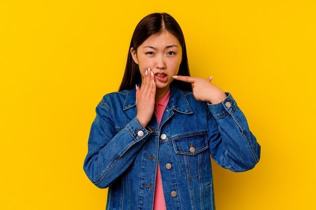 Jonge chinese vrouw geïsoleerd op geel met een sterke tandenpijn, kiespijn.