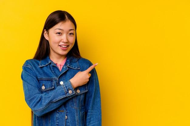 Jonge chinese vrouw geïsoleerd op gele achtergrond glimlachend en opzij wijzend, iets tonen op lege ruimte.