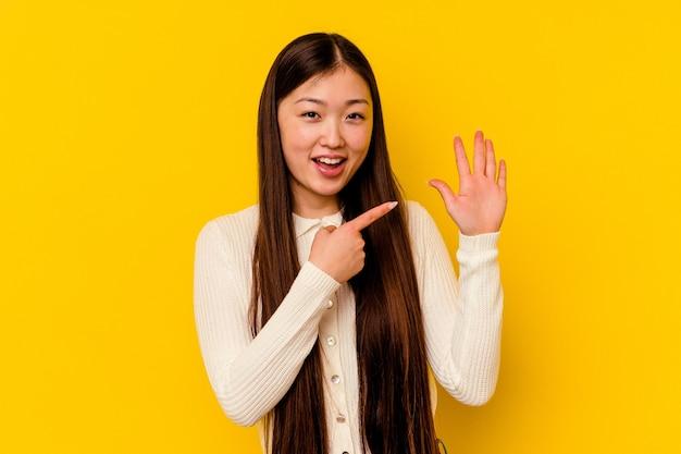 Jonge chinese vrouw geïsoleerd op gele achtergrond glimlachend vrolijk met nummer vijf met vingers.