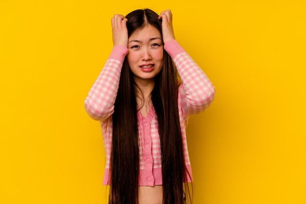 Jonge chinese vrouw geïsoleerd op gele achtergrond huilen, ongelukkig met iets, pijn en verwarring concept.