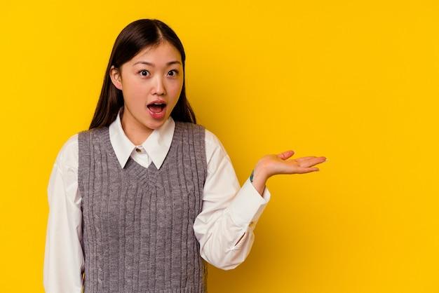 Jonge chinese vrouw geïsoleerd op gele achtergrond onder de indruk de ruimte van het bedrijfskopie op palm.