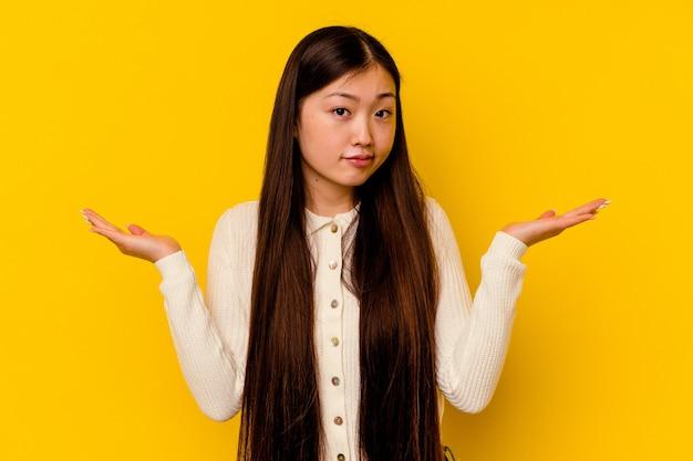 Jonge chinese vrouw geïsoleerd op gele achtergrond verward en twijfelachtig schouders ophalen om een kopie ruimte vast te houden.