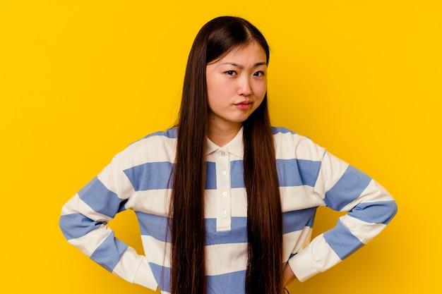 Jonge chinese vrouw geïsoleerd op gele achtergrond verward, twijfelachtig en onzeker.