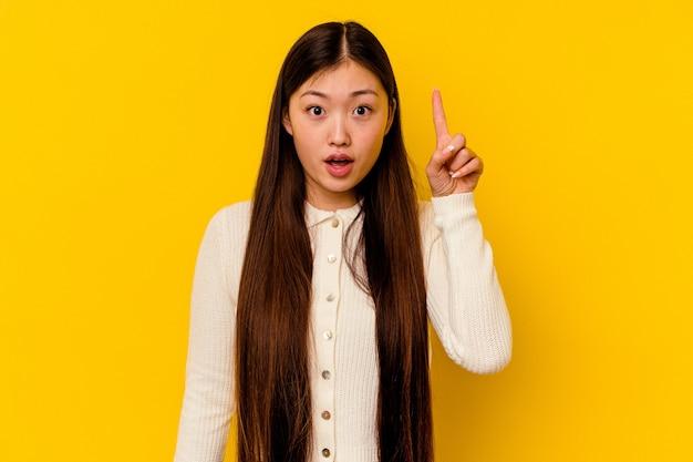 Jonge chinese vrouw geïsoleerd op gele achtergrond wijzend ondersteboven met geopende mond.