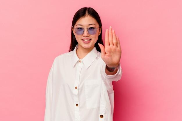 Jonge chinese vrouw geïsoleerd op roze achtergrond glimlachend vrolijk weergegeven: nummer vijf met vingers.