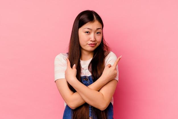 Jonge chinese vrouw geïsoleerd op roze achtergrond wijst zijwaarts, probeert te kiezen tussen twee opties.