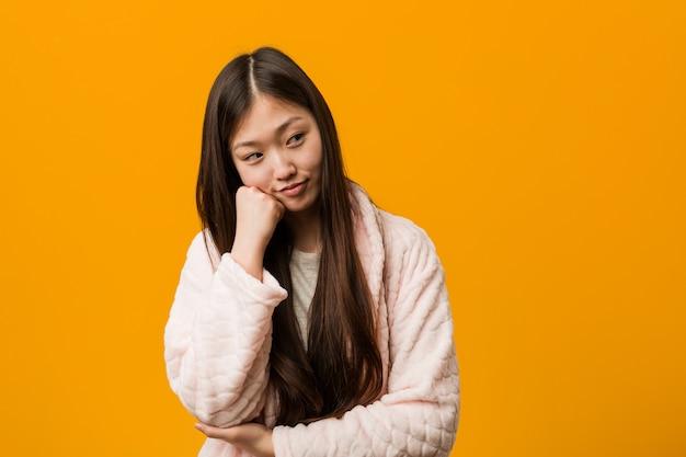 Jonge chinese vrouw in pyjama die droevig en peinzend voelt, bekijkend exemplaarruimte.