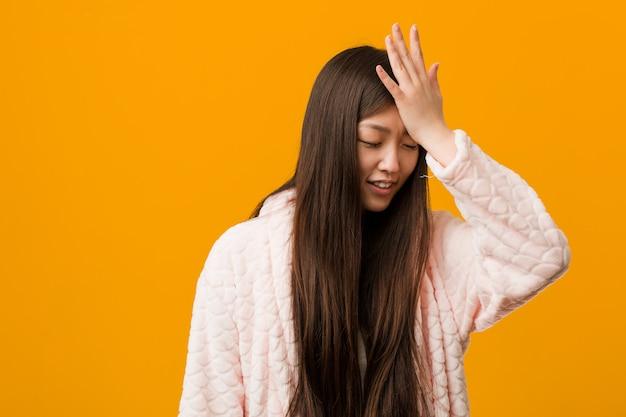 Jonge chinese vrouw in pyjama die iets vergeten, voorhoofd met palm meppen en ogen sluiten.