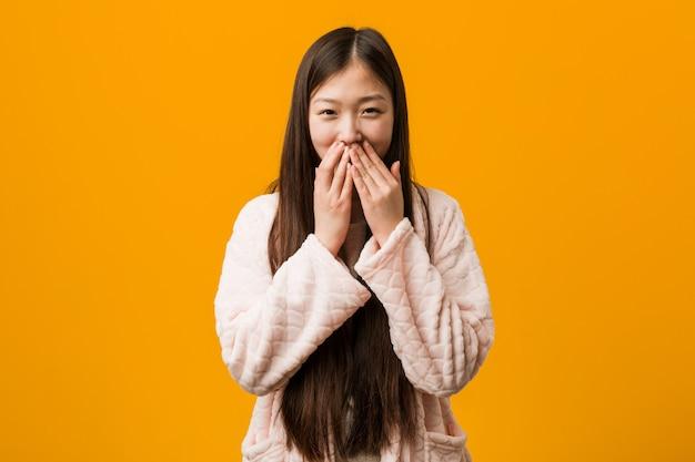 Jonge chinese vrouw in pyjama die om iets lacht, die mond behandelt met handen.