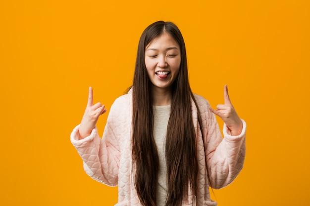 Jonge chinese vrouw in pyjama die rotsgebaar met vingers tonen