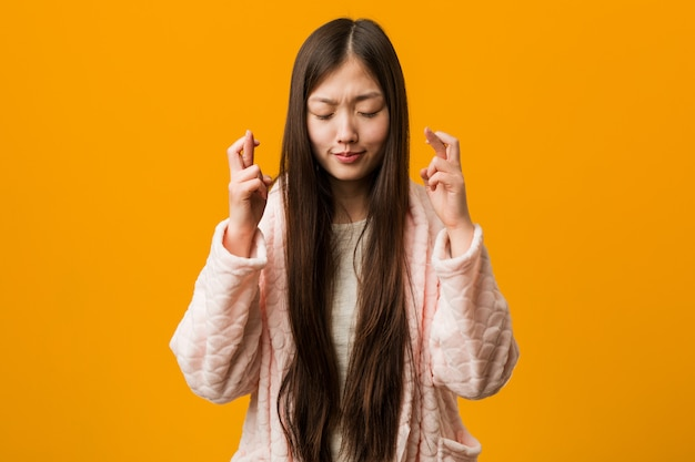 Jonge chinese vrouw in pyjama die vingers kruisen voor het hebben van geluk