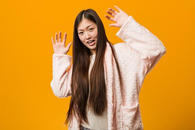 Jonge chinese vrouw in pyjama die wordt geschokt wegens een dreigend gevaar