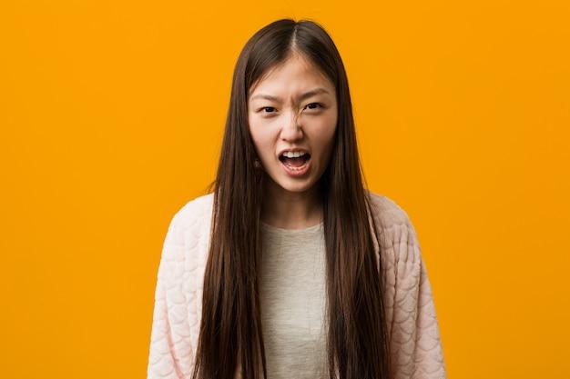 Jonge chinese vrouw in pyjama die zeer boos en agressief gilt.