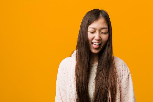 Jonge chinese vrouw in pyjama grappig en vriendelijk steekt hem tong uit.