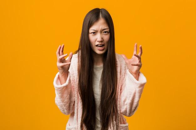 Jonge chinese vrouw in pyjama overstuur schreeuwen met gespannen handen.