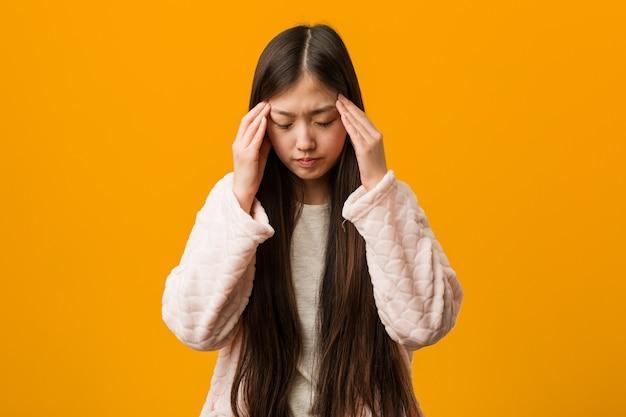 Jonge chinese vrouw in pyjama tempels aan te raken en hoofdpijn te hebben.