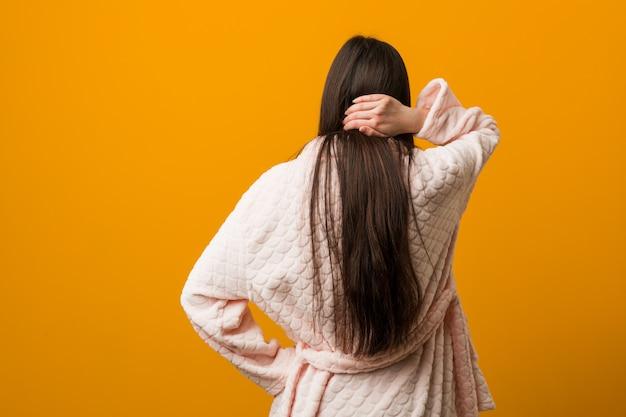 Jonge chinese vrouw in pyjama van achter het denken over iets.