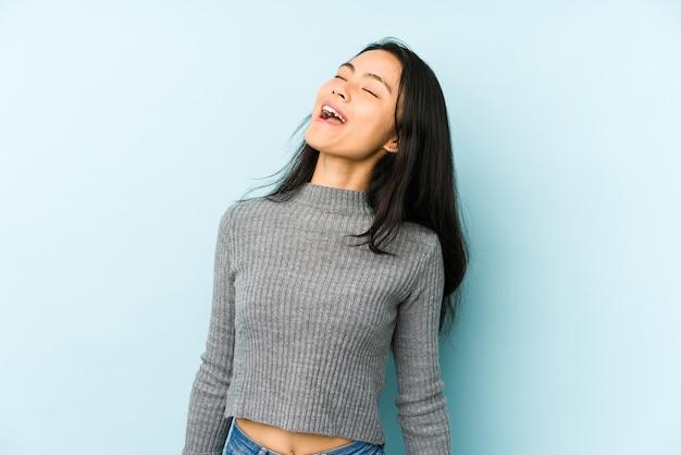 Jonge chinese vrouw ontspannen en gelukkig lachen, nek uitgerekt met tanden.