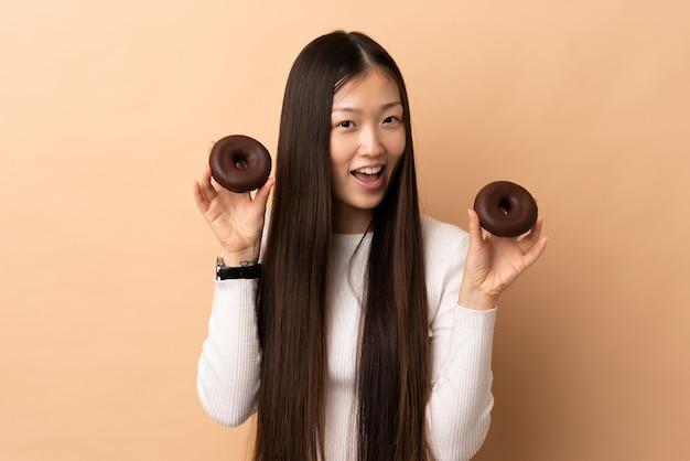 Jonge chinese vrouw op geïsoleerde holdingsdonuts met gelukkige uitdrukking